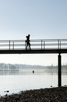 Germany, Baden-Wuerttemberg, Constance District, Lake Constance, Mainau, woman walking on jetty - JED000155