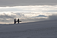 Germany, Eschach, Snowboarders walking in snow - JED000143
