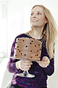 Young woman holding cake stand with chocolate cake - MFF000890