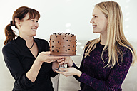 Two smiling women exchanging cake stand with chocolate cake - MFF000895