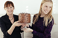 Two smiling women exchanging cake stand with chocolate cake - MFF000896