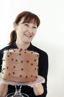 Portrait of smiling woman holding cake stand with chocolate cake - MFF000897