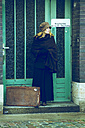 Woman with old suitcase waiting - NG000123