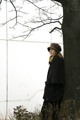 Woman leaning against tree trunk - NG000093