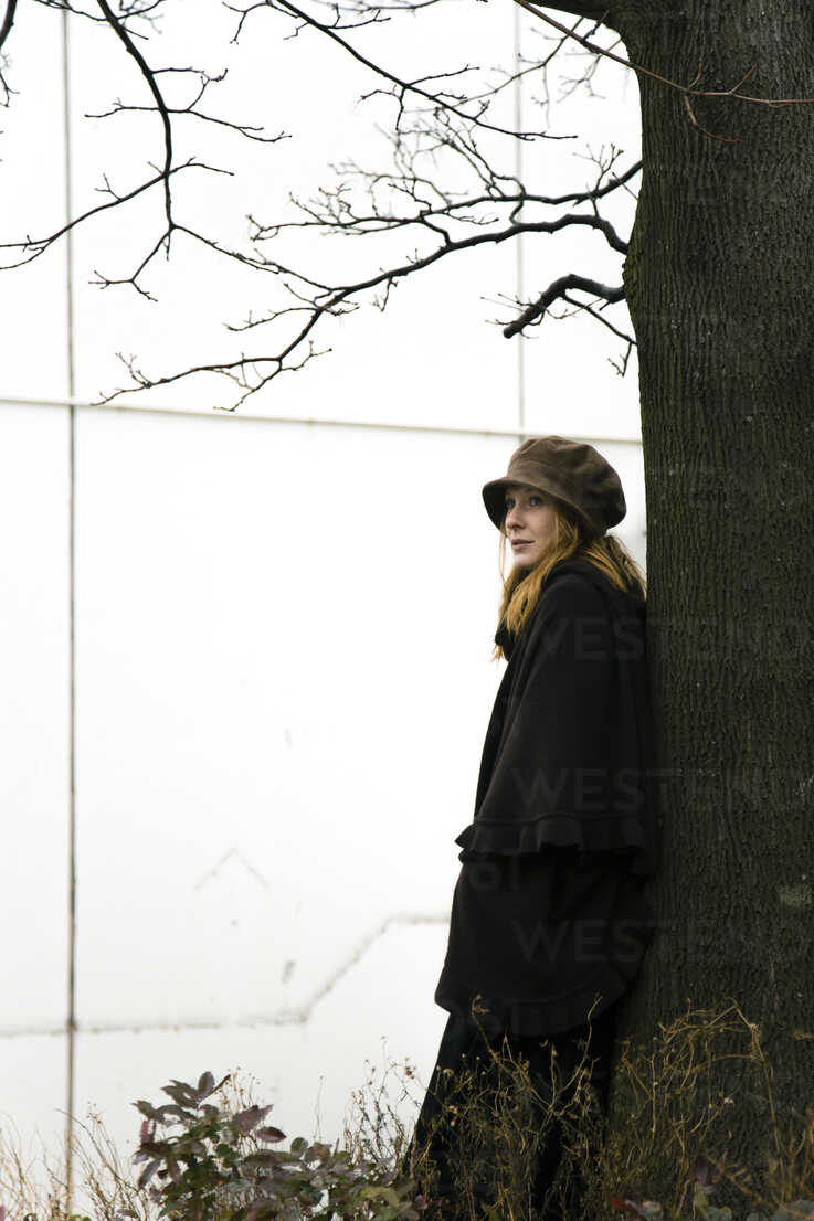 Woman leaning against tree trunk - NG000093 - Nadine Ginzel/Westend61