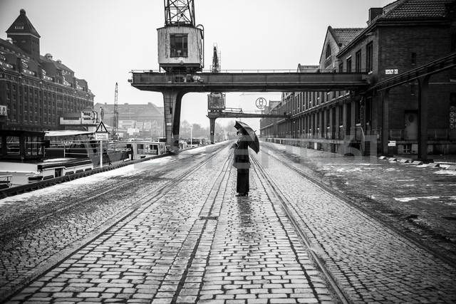 Germany, Berlin, woman with umbrella watching buildings at industrial harbour - NG000094 - Nadine Ginzel/Westend61