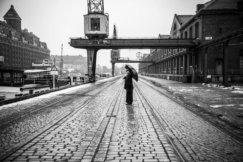 Germany, Berlin, woman with umbrella watching buildings at industrial harbour - NG000094