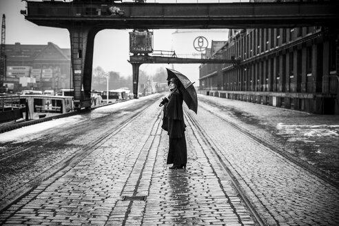Germany, Berlin, woman with umbrella watching buildings at industrial harbour - NG000095