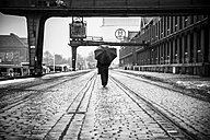 Germany, Berlin, woman with umbrella walking at industrial harbour - NG000097