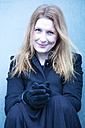 Portrait of smiling woman wearing gloves - NG000102