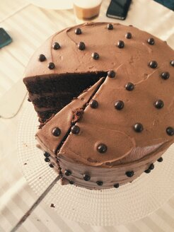 Chocolate cake with frosting and a missing piece on a table - MEAF000162