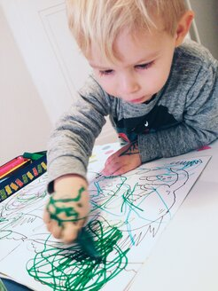 Little boy with smeared hands drawing in a coloring book - MEAF000173
