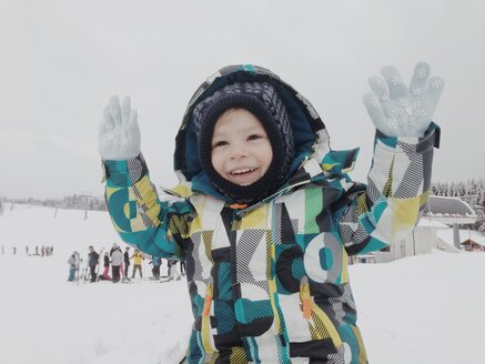 Happy boy lifting his hands in snow outfit - MEAF000185