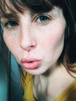 Close-up of woman with freckles blowing a kiss - MEAF000209
