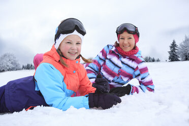Germany, Masserberg, Mother and daughter lying in snow, smiling happily - VTF000095