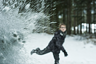 Boy throwing snowball against  windscreen - PAF000421
