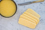 Bowl of corn semolina, knife and sliced polenta on white marble - LVF000722
