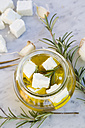 Glass of diced sheep cheese pickled in olive oil and rosmary on white marble - LVF000723