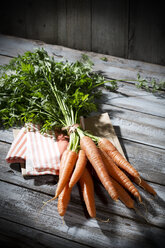 Bunch of organic carrots on cloth and grey wooden table - MAEF007956