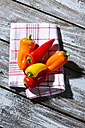 Red, orange and yellow bell peppers on kitchen towel and wooden table - MAEF007957