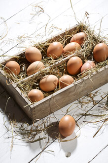 Wooden box of brown eggs and hay on white wooden table - MAEF007948