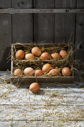 Wooden box of brown eggs and hay leaning on wooden wall - MAEF007943