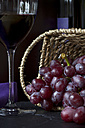 Wicker basket of red grapes (vitis vinifera), red wine glass and bottle in the background - YFF000046