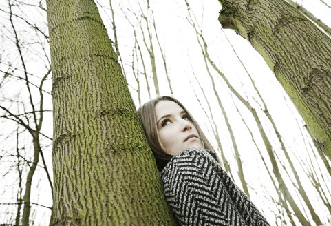 Portrait of teenage girl leaning against tree trunk - JATF000675