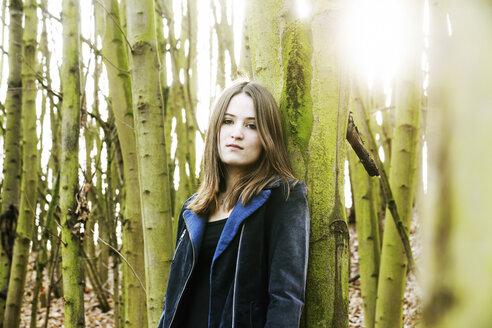 Portrait of teenage girl leaning against tree trunk - JATF000669