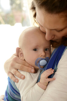 Mother carrying her baby boy in a baby sling - BFRF000356