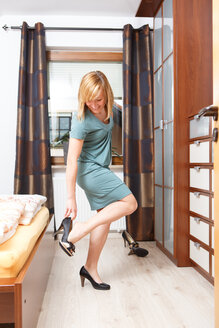 Smiling woman getting dressed with pumps in her bedroom - VTF000112