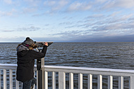 Germany, Cuxhaven, Tourist looking through binoculars - FOF006344