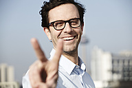 Portrait of smiling man showing victory sign - FMK000960