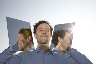 Portrait of smiling man holding two mirrors - FMK000981