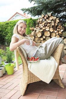 Portrait of smiling teenage girl sitting on wicker chair in the garden - VTF000117