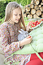 Smiling girl feeding rabbit with strawberries - VTF000116