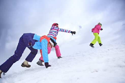 Two teenage girls and her mother having a snowball fight - VTF000113