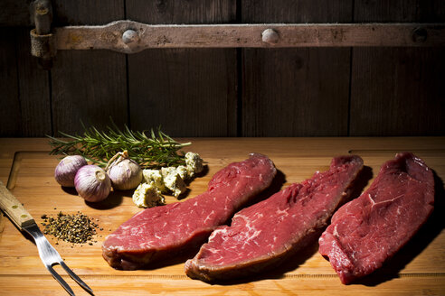 Beefsteak, garlic, rosemary, herb butter and pepper on chopping board - MAEF007987
