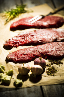Beefsteak, garlic, rosemary, herb butter and pepper on baking paper - MAEF007982