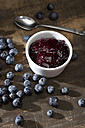 Bowl of blueberry and raspberry jam, spoon and blueberries on dark wooden table - MAEF008018