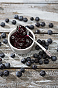 Bowl of blueberry and raspberry jam, spoon and blueberries on wooden table - MAEF008011
