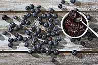 Bowl of blueberry and raspberry jam, spoon and blueberries on wooden table, elevated view - MAEF008010