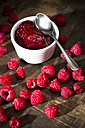 Bowl of raspberry jam, spoon and raspberries on wooden table - MAEF008006
