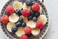 Plate of blueberries, raspberries and banana slices on wooden table - SARF000278