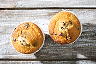 Two muffins in paper cups on grey wooden table, elevated view - MAEF008045