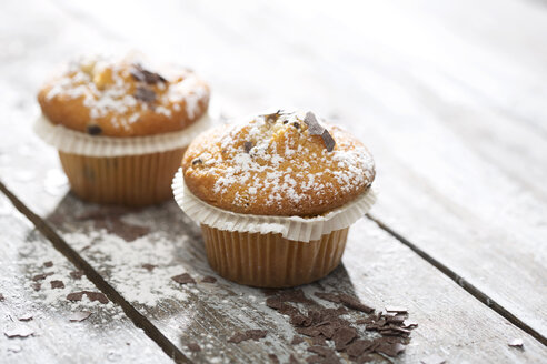 Two muffins in paper cups sprinkled with powdered sugar and chocolate shavings on wooden table - MAEF008047
