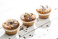 Three muffins in paper cups sprinkled with powdered sugar and chocolate shavings on white wooden table - MAEF008059