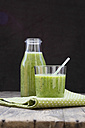 Glass bottle and glass of green smoothie, made of spinach, rocket salad, apple, orange, banana and cucumber, on wooden table - LV000781