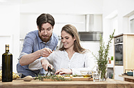Happy couple preparing food in kitchen - FMKF000988