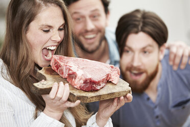 Happy young womanpretending to bite into raw steak - FMKF000998